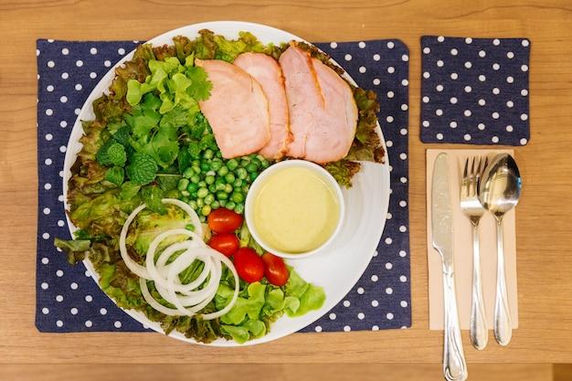 Salade fraîche avec une délicieuse poitrine de poulet, du chêne vert, de la laitue, de l'oignon et des tomates.