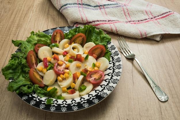 Salade fraîche et exquise de cœurs de palmier coupés en tranches, tomates cerises, grains de maïs, poivron rouge, laitue