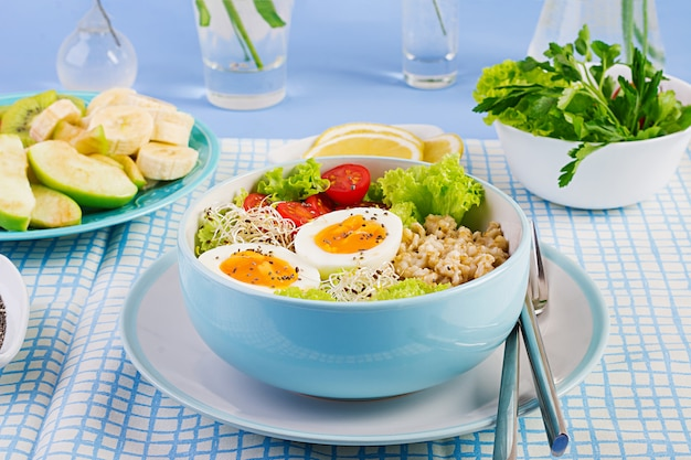 Salade fraîche avec flocons d'avoine, tomates, laitue, micro-légumes et oeuf à la coque et assiette de fruits