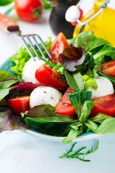 Salade fraîche avec laitue, salade de cresson, roquette, betteraves, tomates, fromage mazarella et olives dans une tasse en céramique sur fond clair. la nourriture saine. mise au point sélective.