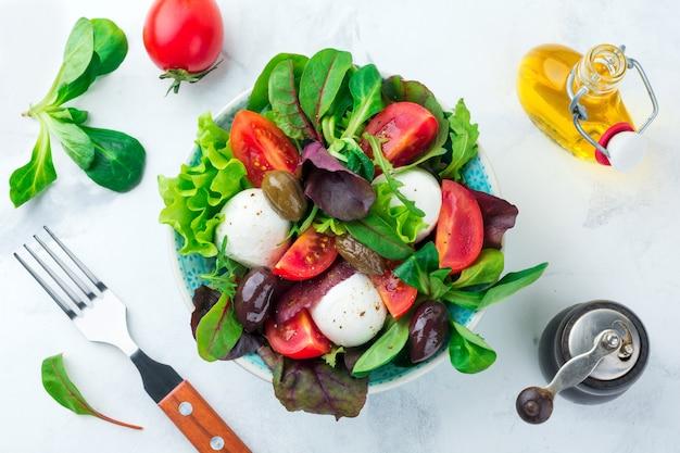 Salade fraîche avec laitue, salade de cresson, roquette, betteraves, tomates, fromage mazarella et olives dans une tasse en céramique sur une surface légère