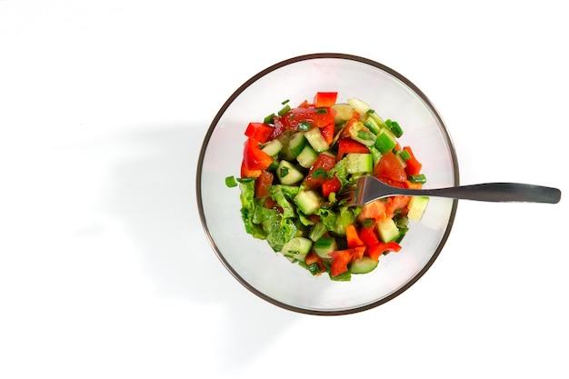 Salade fraîche avec légumes tomates, concombres, laitue, feuilles de salade sur fond blanc vue de dessus et espace de copie. concept d'alimentation et d'alimentation saine. la nourriture végétarienne