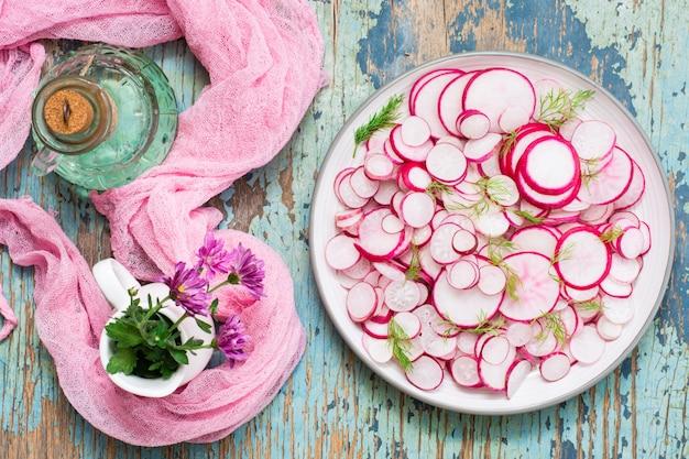Salade fraîche de morceaux de radis et d'aneth sur une assiette sur une table en bois. prêt collation pour un régime