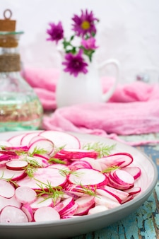 Salade fraîche de morceaux de radis et d'aneth sur une assiette sur une table en bois