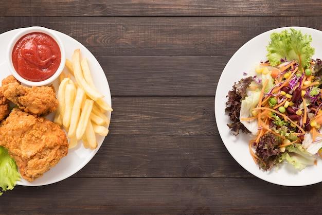 Salade fraîche et poulet frit et frites sur le fond en bois. nourriture contrastée