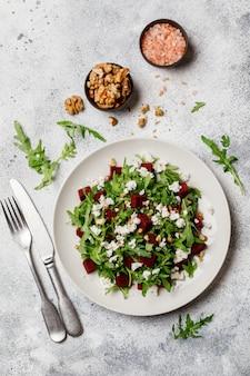 Salade fraîche à la roquette, au fromage feta, aux noix et à la betterave sur une plaque blanche