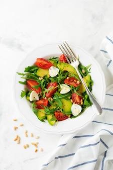 Salade fraîche de roquette, tomate, avocat, huile d'olive, noix et œufs de caille sur fond de pierre claire