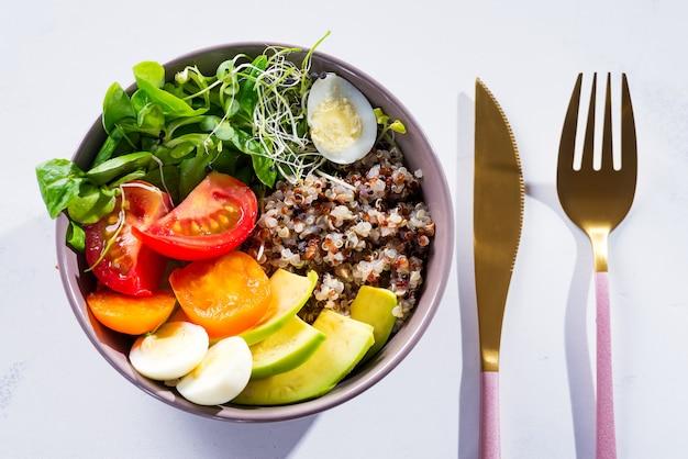 Salade fraîche saine avec du quinoa, des tomates cerises et un mélange de légumes verts, avocat, oeuf et micro légumes verts sur du marbre