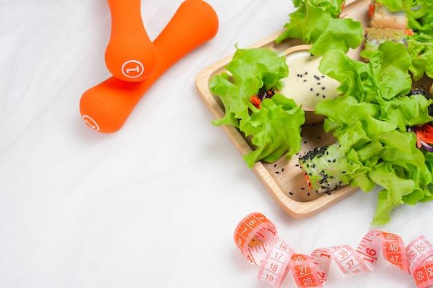 Salade fraîche et saine, ruban à mesurer et haltères