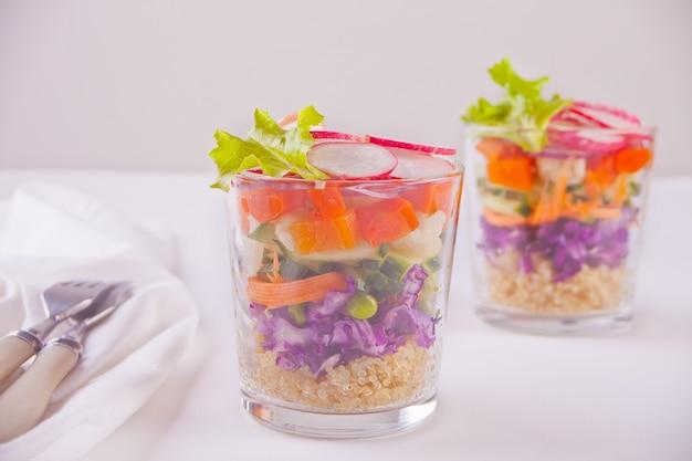 Salade fraîche saine en verre avec chou rouge, tomate, quinoa, salade verte et radis sur la table blanche