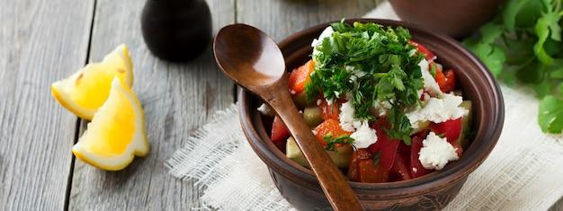 Salade fraîche shopska de poivrons au four, tomate, oignon, concombre, persil, aneth et fromage feta dans un bol en céramique. cuisine traditionnelle serbe. mise au point sélective.