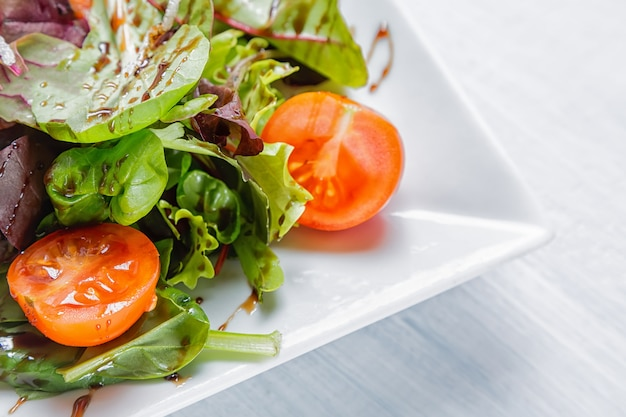 Salade fraîche de tomates cerises, laitue et sauce sur une assiette blanche
