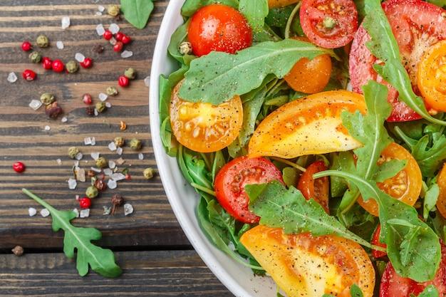 Salade fraîche de tomates rouges, roses et jaunes avec de la roquette et des épices dans une assiette blanche sur une table en bois sombre,