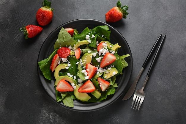 Salade de fraises aux épinards, fromage feta, avocat, vinaigre balsamique et huile d'olive dans une assiette