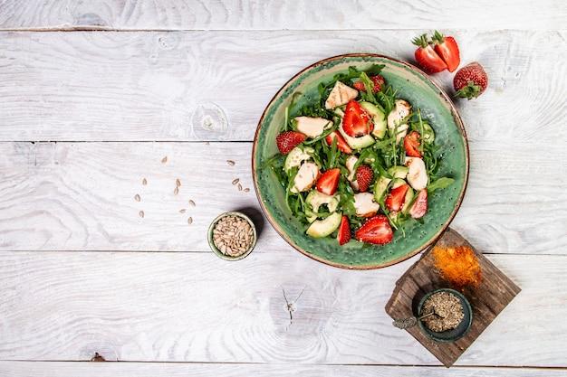 Salade de fraises fraîches avec roquette, poulet, avocat et fraises. assiette avec un aliment diététique céto. vue de dessus