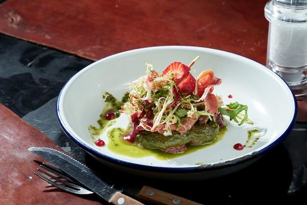 Salade de fraises, prosciutto, sauce pesto dans une assiette blanche. surface sombre. lumière forte