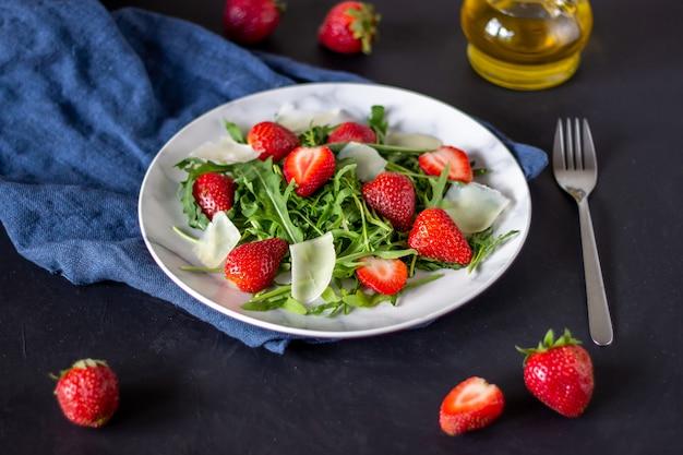 Salade de fraises, de roquette et de fromage sur fond sombre. aliments diététiques.