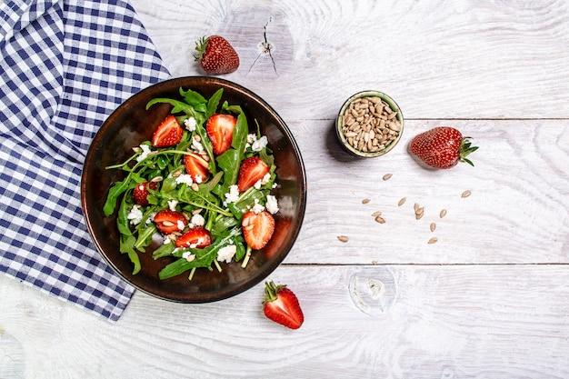 Salade de fraises à la roquette et ricotta, fond de bois blanc, format bannière longue, vue du dessus