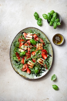 Salade de fraises, tomates, roquette et fromage halloumi