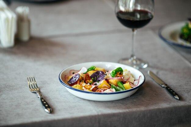 Salade de fromage frit légumes verre de vin rouge