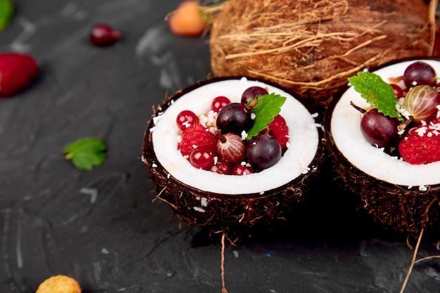 Salade de fruits agrus, groseille à maquereau, framboise dans un bol en coquille de noix de coco