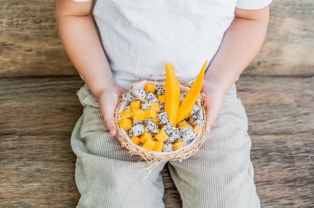 Salade de fruits aux fruits du dragon et papaye dans une demi-noix de coco à la main