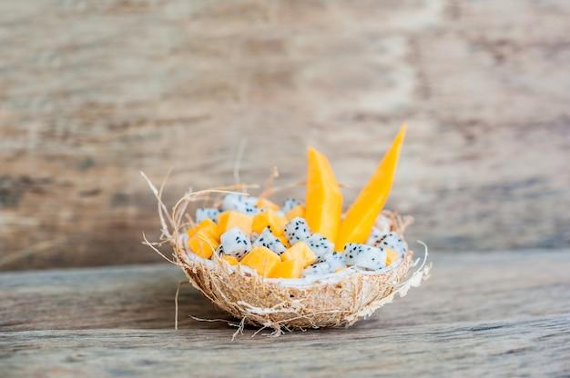Salade de fruits aux fruits du dragon et papaye dans une demi-noix de coco