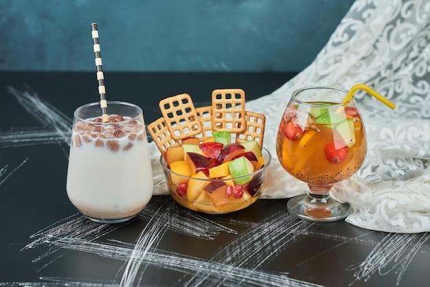 Salade de fruits avec des craquelins et des boissons.