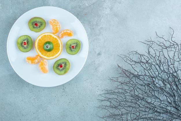 Salade de fruits dans une assiette blanche sur bleu décoratif.