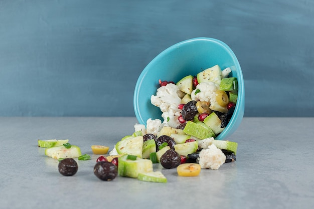 Salade de fruits dans une tasse bleue aux olives noires.