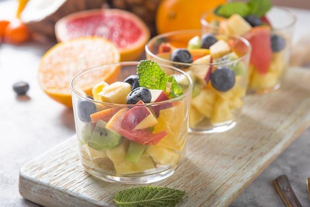 Salade de fruits dans des verres, aliments frais d'été, sains bio orange kiwi myrtilles ananas noix de coco