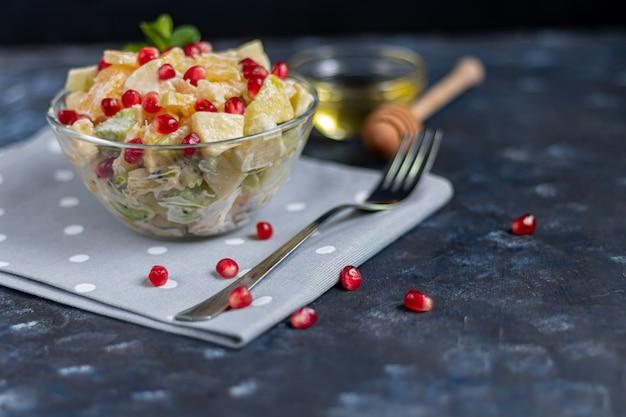Salade de fruits diététique pour le petit déjeuner. kiwi orange banane et pomme coupée en dés et assaisonnée de yaourt au miel.