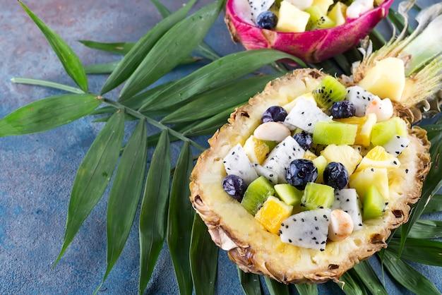 Salade de fruits exotiques servie dans un demi ananas sur des feuilles de palmier sur fond de pierre