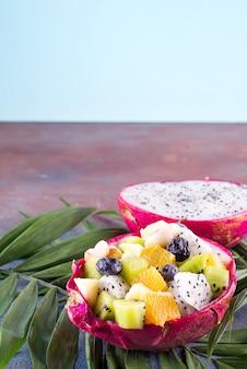 Salade de fruits exotiques servie dans un demi-fruit du dragon sur des feuilles de palmier sur fond de pierre, espace copie