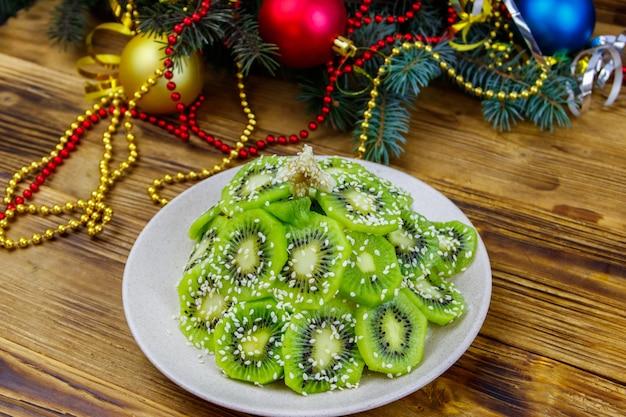 Salade de fruits en forme d'arbre de noël et décorations de noël sur table en bois. idée créative pour les desserts festifs de noël et du nouvel an. idée de nourriture amusante pour les enfants