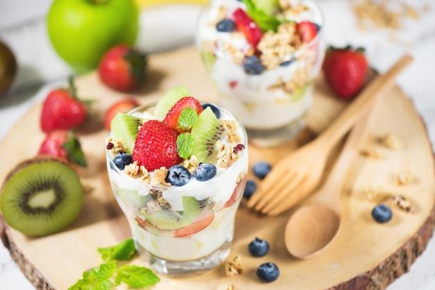 Salade de fruits frais au yaourt et baies en verre sur une plaque en bois
