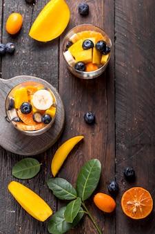 Salade de fruits frais avec divers types de baies et d'agrumes, mangue servie dans un bol en verre, placé sur une table en bois
