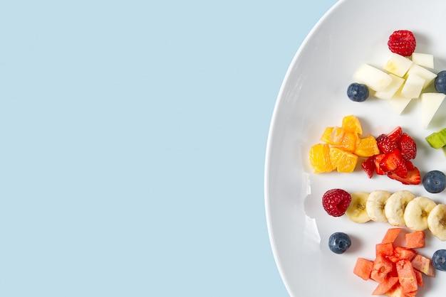 Salade de fruits frais sur plaque blanche.