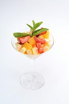 Salade de fruits avec fraises, orange, pomme et menthe dans un bécher en verre