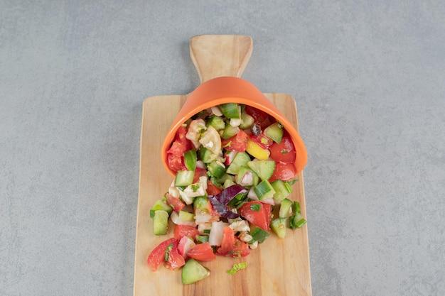 Salade de fruits et légumes hachés sur une planche de bois.