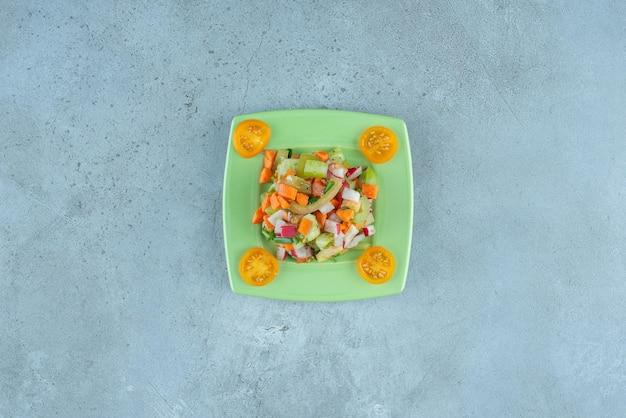 Salade de fruits et légumes avec des ingrédients mélangés sur bleu.