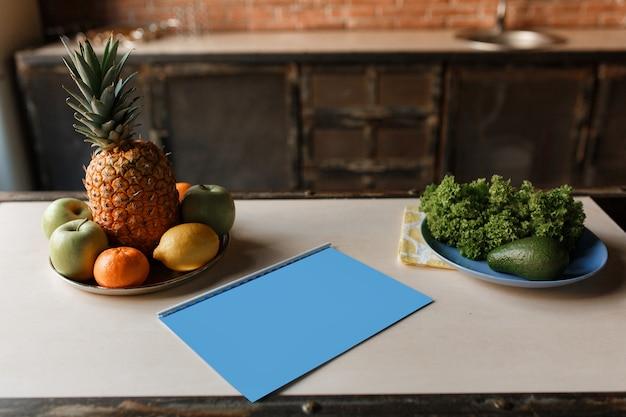 Salade de fruits et légumes sur une table en bois avec carnet et crayon