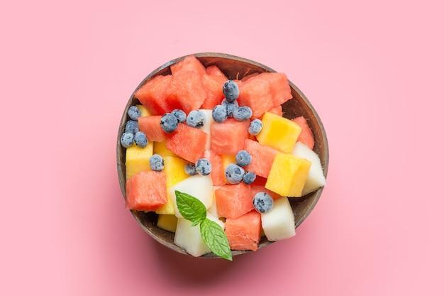 Salade de fruits de melon, pastèque, myrtille dans un bol de noix de coco sur rose