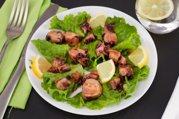 Salade de fruits de mer au citron dans l'assiette et verre d'eau