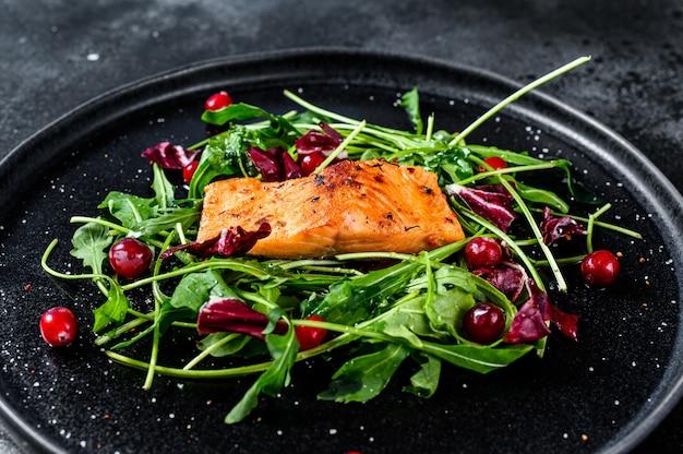Salade de fruits de mer au saumon, roquette, laitue et canneberges. surface noire. vue de dessus
