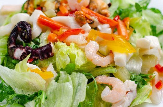 Salade de fruits de mer aux légumes et laitue sur plaque blanche