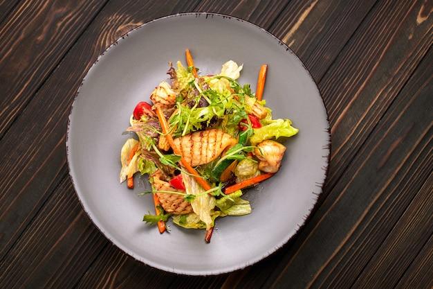 Salade de fruits de mer avec calamars grillés, maïs, carottes, tomates et laitue, sur une plaque grise, sur une table en bois