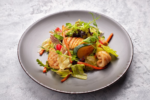 Salade de fruits de mer avec calamars grillés, maïs, carottes, tomates et laitue, sur une plaque grise