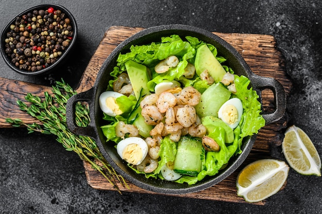 Salade de fruits de mer avec crevettes grillées, crevettes, œuf, avocat et concombre dans une poêle. table en bois sombre. vue de dessus.