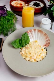 Salade de fruits de mer décorée de coquille et servie avec du fromage râpé et des légumes verts